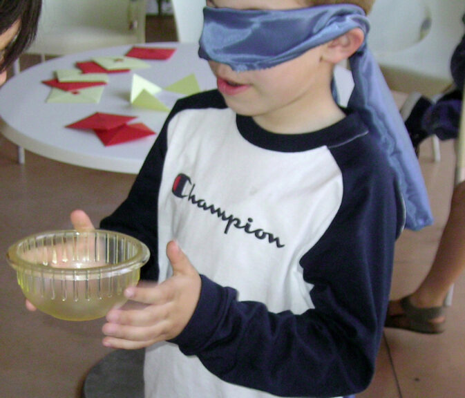 a child touching a bowl without looking at it